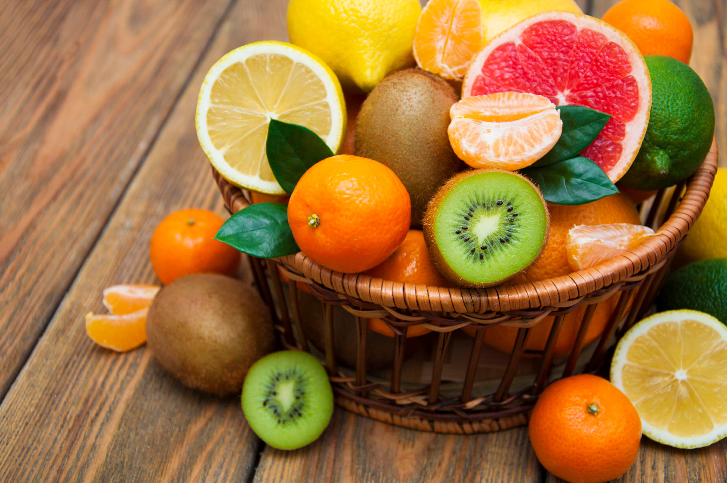 52315233 – fresh juicy citrus fruits in a basket on a wooden background